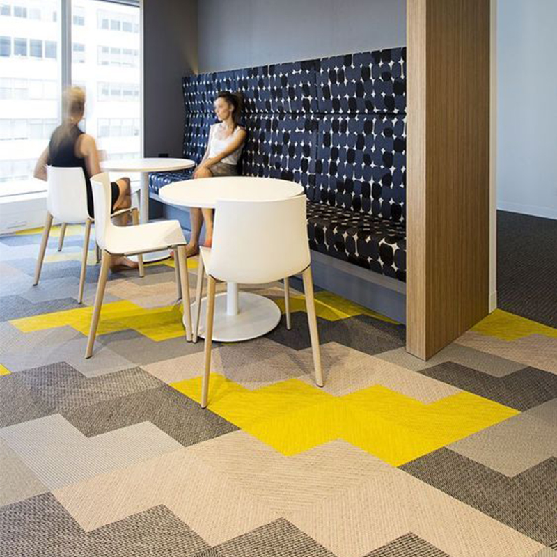 Pattern for breakout area using shades of grey and yellow carpet tiles